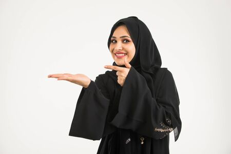 Middle eastern woman with traditional emirates dresses posing in a photographic studio - Concepts about lifestyle, happiness and family relationship in the UAE