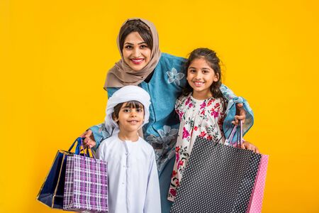Middle eastern family with traditional emirates dresses posing in a photographic studio - Concepts about lifestyle, happiness and family relationship in the UAE Stock Photo