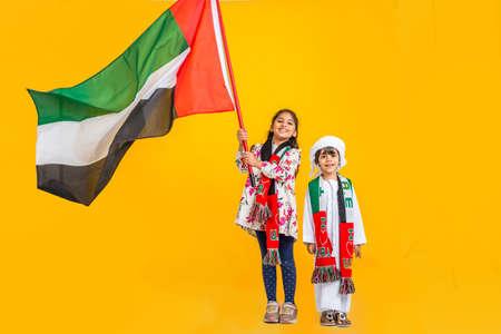 穿着传统阿联酋服装的中东家庭举着一面旗帜