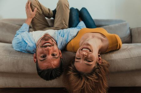 Young couple spending time together at home. Man and woman sitting on the couch and having fun