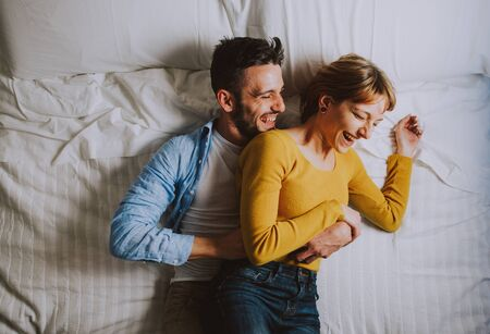 young couple relaxing in bed and having fun.