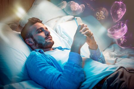 Man texting on the phone while lying down in bed Stock Photo