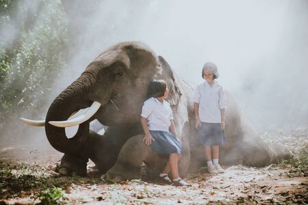 Thai  girls playing after school in the jungle near their elephant friend