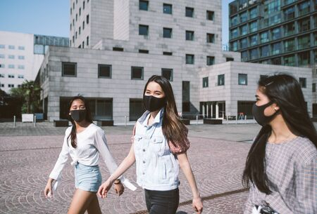 Group of asian girls going out after quarantine during coronavirus period. Young women outdoor with safety masks