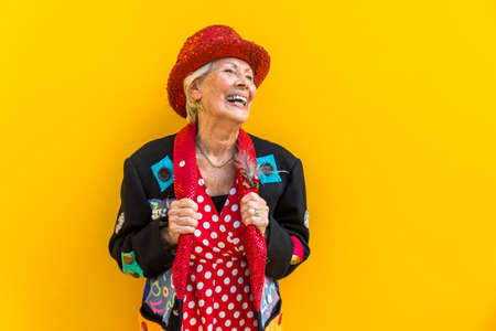 Happy and playful senior woman having fun - Portrait of a beautiful lady above 70 years old with stylish clothes, concepts about senior people 免版税图像