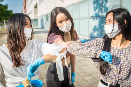 Asian girls with face masks bonding outdoors during pandemic and social distance era - Concepts about quarantine, prevention and covid-19 Stock fotó