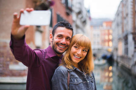 Beatiful young couple having fun while visiting Venice - Tourists travelling in Italy and sightseeing the most relevant landmarks of Venezia - Concepts about lifestyle, travel, tourism Banque d'images