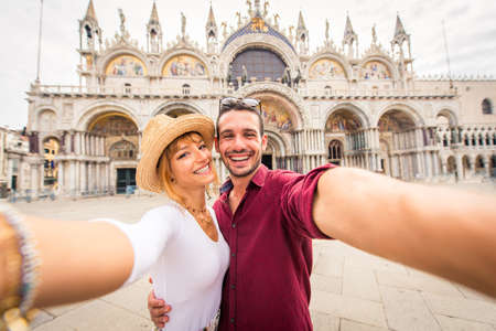 Beatiful young couple having fun while visiting Venice - Tourists travelling in Italy and sightseeing the most relevant landmarks of Venezia - Concepts about lifestyle, travel, tourism