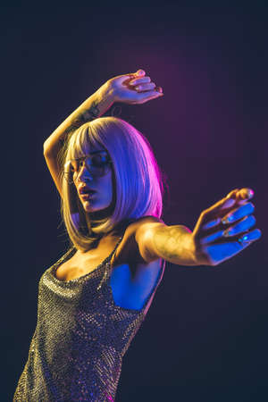 Young woman with gray hair dancing and celebrate. Colored gel portraits