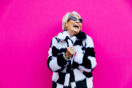 Happy grandmother posing on colored backgrounds. Woman having fun and celebrating Foto de archivo