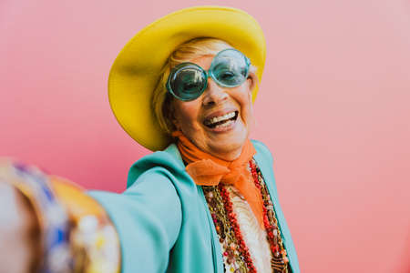 Happy grandmother posing on colored backgrounds. Woman having fun and celebrating