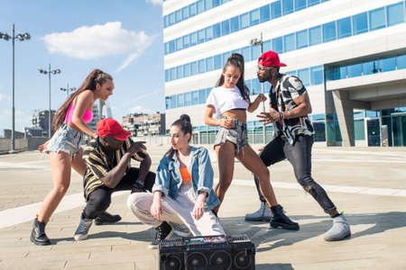 Group of hip hop dancers permorming their dance. Crew making show in an urban place 版權商用圖片