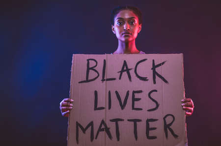 Black lives matter concept. white human arm painted in black on yellow colored background. 写真素材