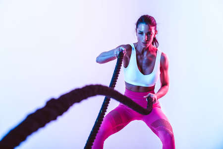 Fit woman training hard with ropes. Girl making exercizes in the gym. Concept about bodybuilding and lifestyle