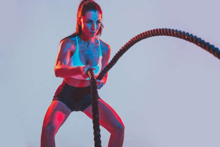 Fit woman training hard with ropes. Girl making exercizes in the gym. Concept about bodybuilding and lifestyle Archivio Fotografico