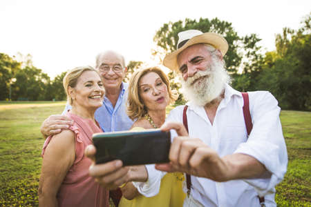 Group of youthful seniors having fun outdoors - Four pensioners bonding outdoors, concepts about lifestyle and elderly Imagens
