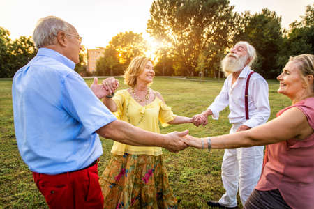 Group of youthful seniors having fun outdoors - Four pensioners bonding outdoors, concepts about lifestyle and elderly Standard-Bild