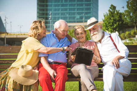 Group of youthful seniors having fun outdoors - Four pensioners bonding outdoors, concepts about lifestyle and elderly Foto de archivo