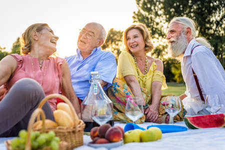 Group of youthful seniors having fun outdoors - Four pensioners bonding outdoors, concepts about lifestyle and elderly