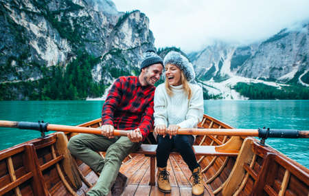 Mountain stories. Happy couple on a wanderlust vacation. Boyfriend and girlfriend spending time together at the lake. Storytelling concept about lifestyle and winter travels