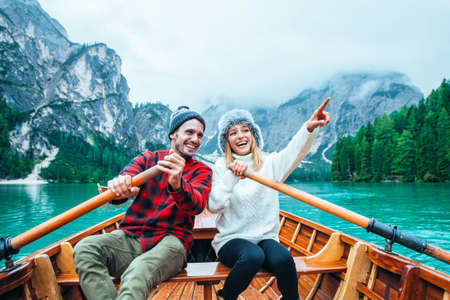 Mountain stories. Happy couple on a wanderlust vacation. Boyfriend and girlfriend spending time together at the lake. Storytelling concept about lifestyle and winter travels Banco de Imagens