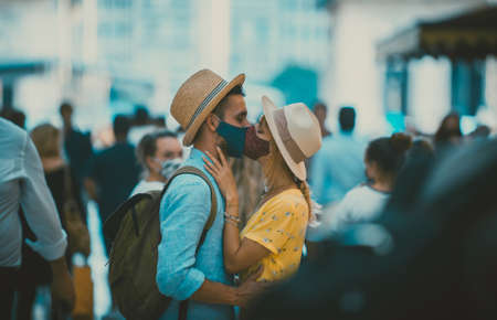 Image of a happy couple on vacation. Young man and woman kissing in the crowd
