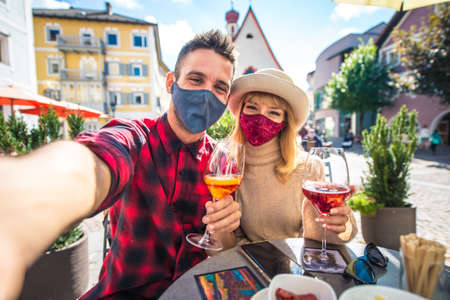 Happy couple taking an aperitif in a cafè. Man and woman on their honeymoon travel on the italian dolomites. Visiting a traditional village in a mountain location