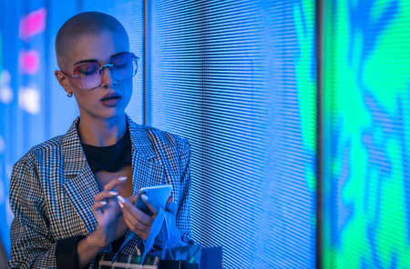 Image of a beautiful young woman posing against a led panel. Shaved head teenager with alternative look making urban portraits Stock Photo