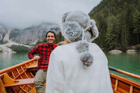Beautiful couple of young adults visiting an alpine lake at Braies, Italy - Tourists with hiking outfit having fun on vacation during autumn foliage - Concepts about travel, lifestyle and wanderlust