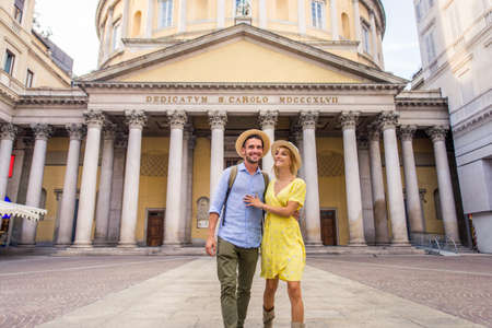 Beautiful couple of lovers sightseeing a famous landmark - Playful tourists visiting a famous european city