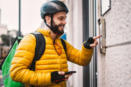 Food delivery rider on his bicycle. Image of a middle age man at work in the city center. Delivering pizza and burgers at home with the thermal backpack