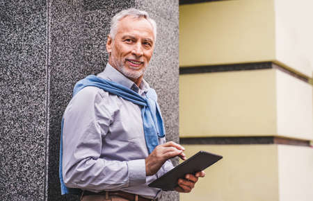 Cheerful senior man portrait - Mature adult using his computer laptop in a bar coffeehouse, concepts about lifestyle, senior people, technology and smart working