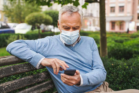 Handsome senior adult with face mask in a park during corona virus pandemic quarantine, concepts about social distancing and elderly