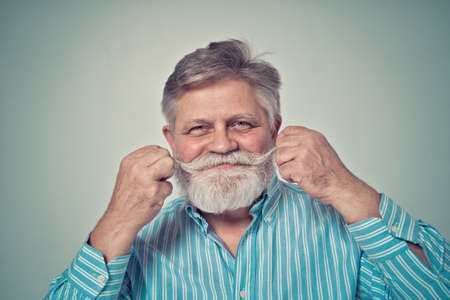 Funny senior man posing in a photoshooting. Happy hipster doing funny expressions. Concept about people and lifestyle.