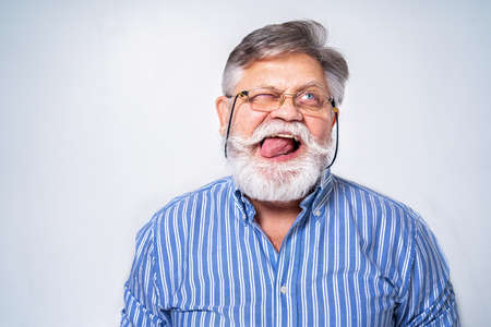 Eccentric senior man with funny expression portrait on background - Active and youthful old male Standard-Bild