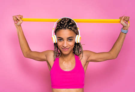 Beautiful afroamerican woman with pigtails portrait on colored background doing sport exercises - Sportive girl wearing sportswear training
