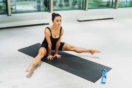 Beautiful athletic woman training in a gym, doing stretching exercises before the workout - Pretty young girl training alone