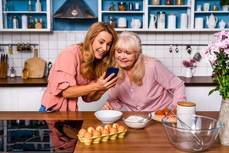 Beautiful senior woman and daughter baking in the kitchen - Grandmother preparing desserts at home with family and looking at recipe on the internet, concepts about cooking, healthy eating and technology