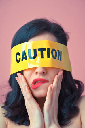 Cinematic image of a woman with a yellow tape on her face. Abstract fine art concept