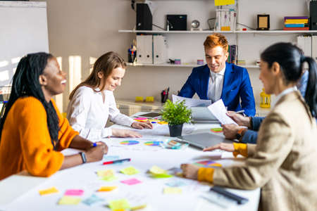 Project managers and employees brainstorming on ideas - Multi-ethnic group of workers having business meeting in a start-up office