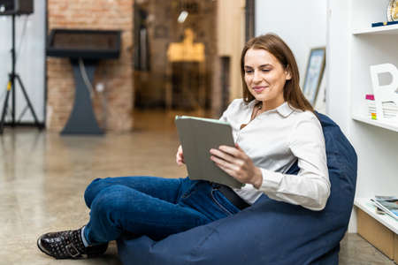 Business company employee working in the relax area - Entrepreneur with colored smart casual clothes working alone in a start-up office Archivio Fotografico