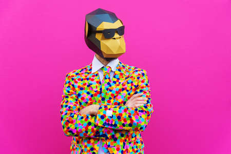 Happy man with funny low poly mask on colored background - Creative conceptual idea for advertising, adult with low-poly origami paper mask doing funny poses Archivio Fotografico