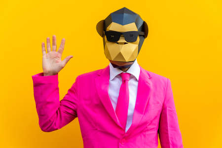 Happy man with funny low poly mask on colored background - Creative conceptual idea for advertising, adult with low-poly origami paper mask doing funny poses