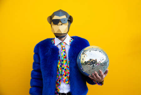 Happy man with funny low poly mask on colored background - Creative conceptual idea for advertising, adult with low-poly origami paper mask doing funny poses Stock Photo