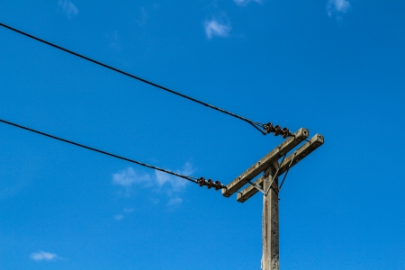 Electricity pole with cables on rich blue sky photo