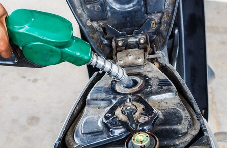 to fill up: The man hand fill up of gasoline in gas station Stock Photo