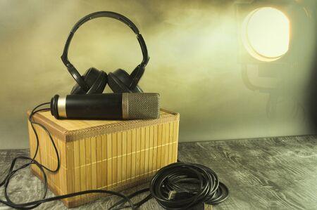 Headphones and microphone in the spotlight. Stok Fotoğraf - 130023774
