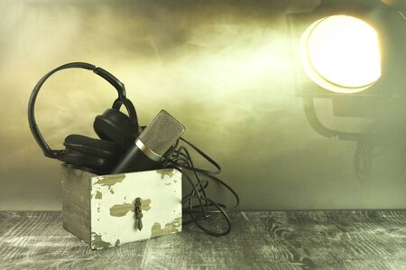 A microphone and headphones in the spotlight. Stok Fotoğraf