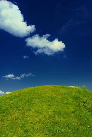 Fresh summer green grass, idyllic hill, deep blue sky