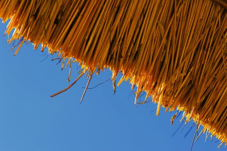 A thatched roof pattern against blue sky Stock Photo